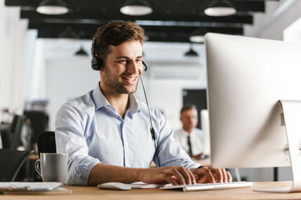 photo-of-businesslike-man-20s-wearing-office-clothes-and-headset-working-on-computer-in-call-center
